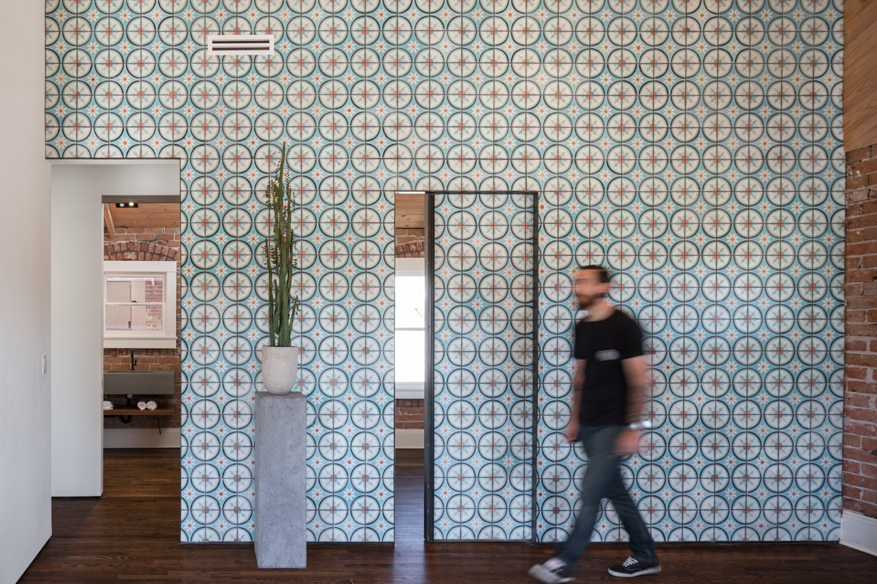 Off the living room, two small bedrooms and a bathroom can be reached through sliding doors that, when closed, continue the cheerful pattern of the Moroccan cement tiles covering the wall.  Photo 4 of 11 in Amazing House is Half Historic and Half Modern