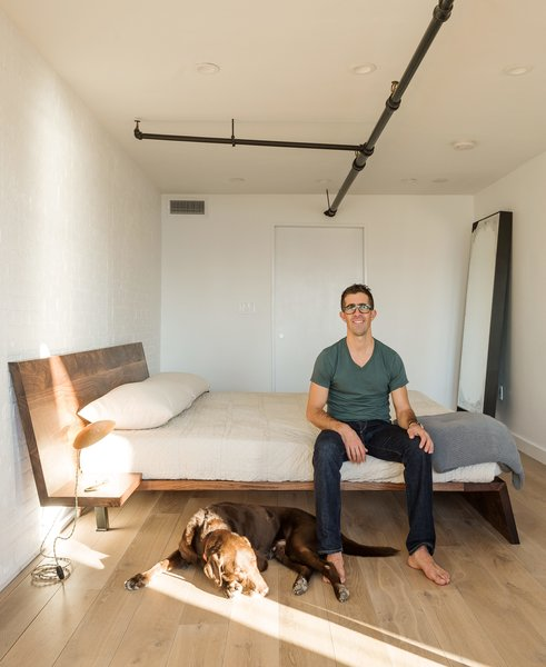 The warm material palette extends to Berryman's bedroom. Like the rest of the apartment, it features work by New York designers, including a custom wood bed by Asher Israelow and a Table Light desk lamp by Lindsey Adelman.