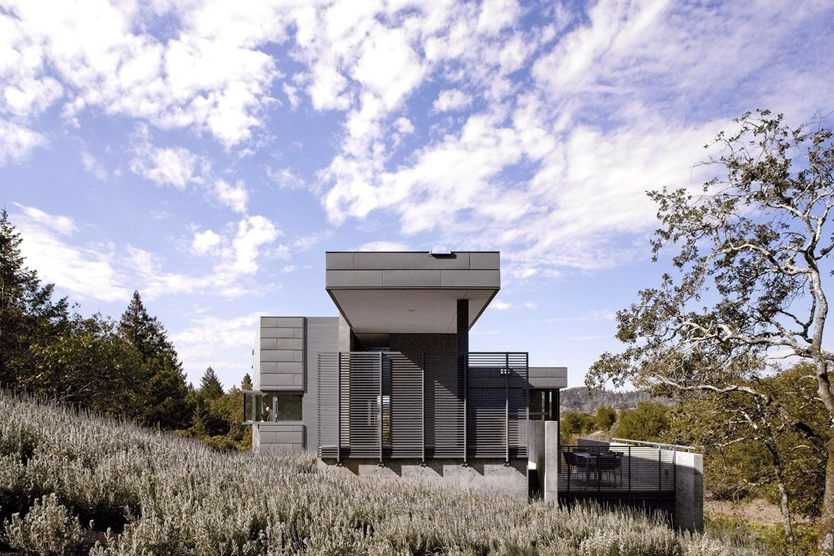 """""""The home's orientation is all about view, facing north out onto the valley over the olive grove,"""" says architect Wendy Evans Joseph. """"Most of the glass is to the north side, limiting heat gain."""" Poured in place concrete, zinc, and stained redwood form the exterior.  A Small, Off-the-Grid Escape in a Sonoma Olive Grove by Tiffany Jow"""
