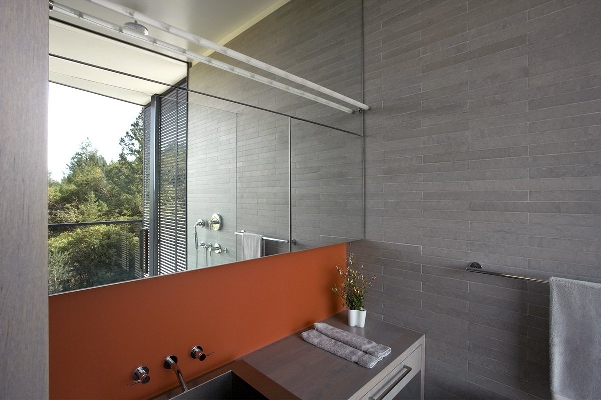 French Blue limestone tile lines the walls of the bathroom, where the shower's glass window takes in views. The orange backsplash, made of 3 Form Chroma, provides a pop of color alongside the Julien sink and Dornbracht fixtures.  A Small, Off-the-Grid Escape in a Sonoma Olive Grove by Tiffany Jow