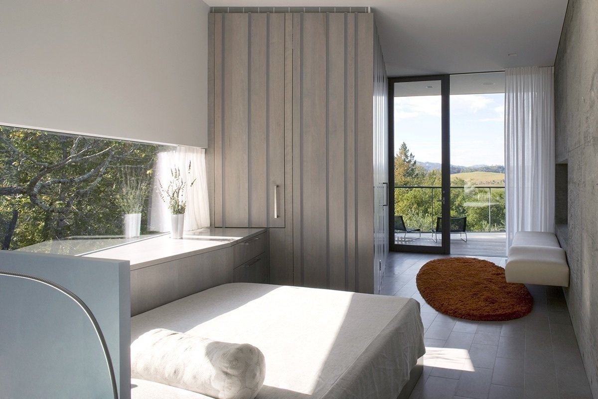 The architects designed the bed, which has a gray-stained oak frame that sits on wheels and features storage underneath. Curtains by Angelique Interiors and a custom rug by Edwards Fields pair well with the room's sheetrock walls.  A Small, Off-the-Grid Escape in a Sonoma Olive Grove by Tiffany Jow