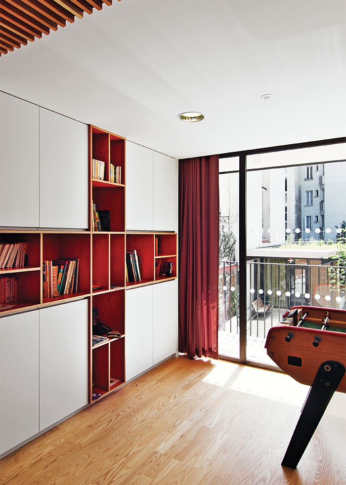 Storage Room and Shelves Storage Type Brambilla designed and crafted the built-in bookcase in a common area from laminated red birch.  Photo 13 of 21 in Red, Red, and More Red! 20 Bold Interiors That Make a Statement from How California Style Influenced a Group Home in Paris