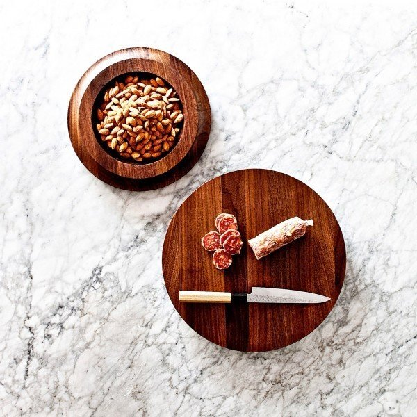 The BlockBowl from On Our Table is a versatile tabletop product that features two distinctive surfaces. The flat circular surface can be used as a cutting board or serving board for cheeses and charcuterie, while the other side features a lipped bowl that can be used to serve nuts, olives, and other snacks.