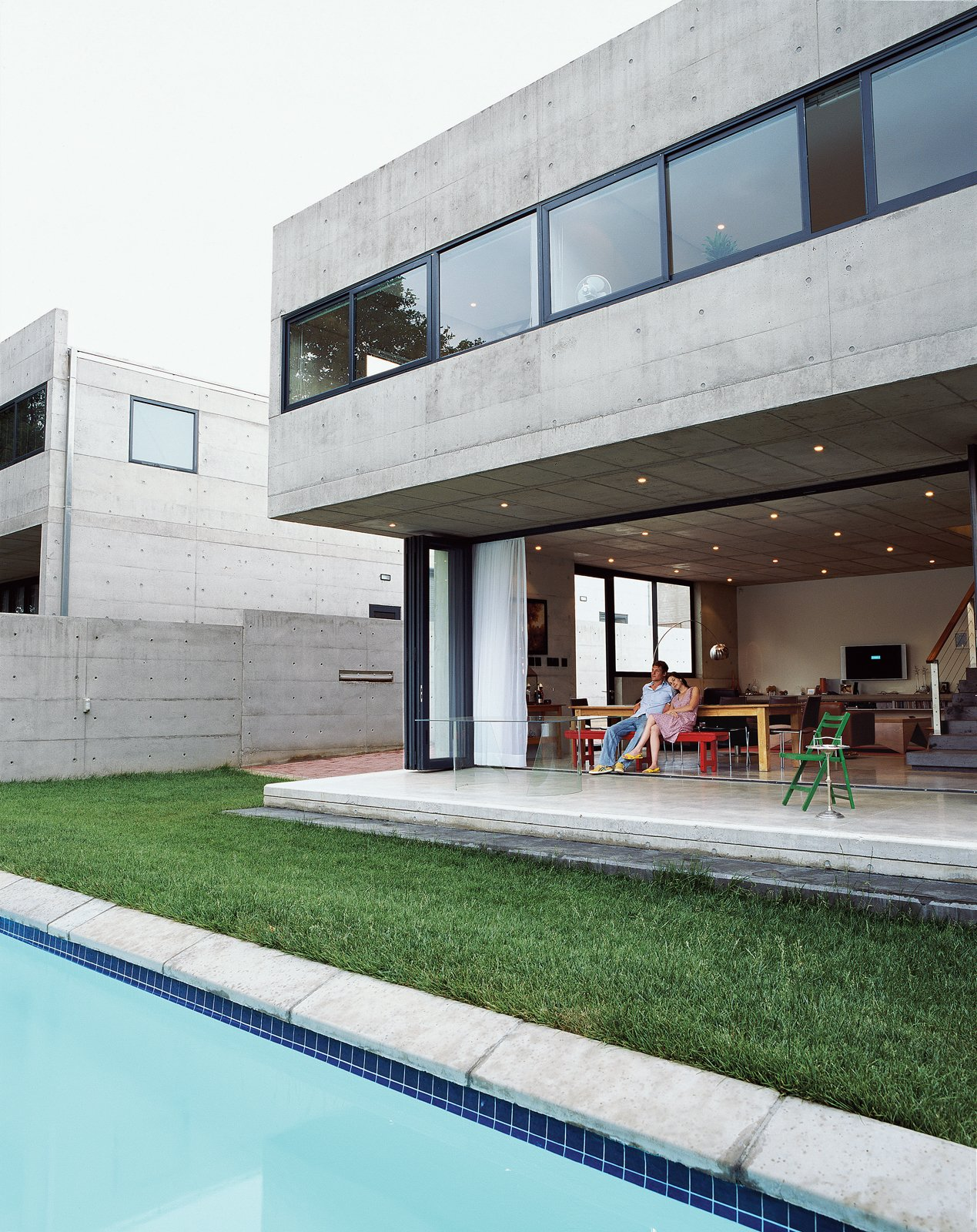 Concrete, Outdoor, Grass, Large, Back Yard, Swimming, Concrete, and Concrete Gregory and Caryn Katz are dwarfed beneath the cantilevered concrete overhang, which houses the bedroom on the upper level. The stackable glass doors that run beneath allow the house to open completely to the yard and swimming pool, soften the severity of the concrete, and blur the boundary between indoors and out.  Best Outdoor Concrete Photos from Katz's Cradle