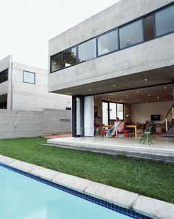 South African architect Gregory Katz designed his own home out of concrete with a cantilevered upper floor that looms over the deck area below. The holes in the precast-concrete panels were poured as anchor holes so that each piece could be lifted into place and installed with anchors, but left exposed in order to create a subtle pattern on the exterior.