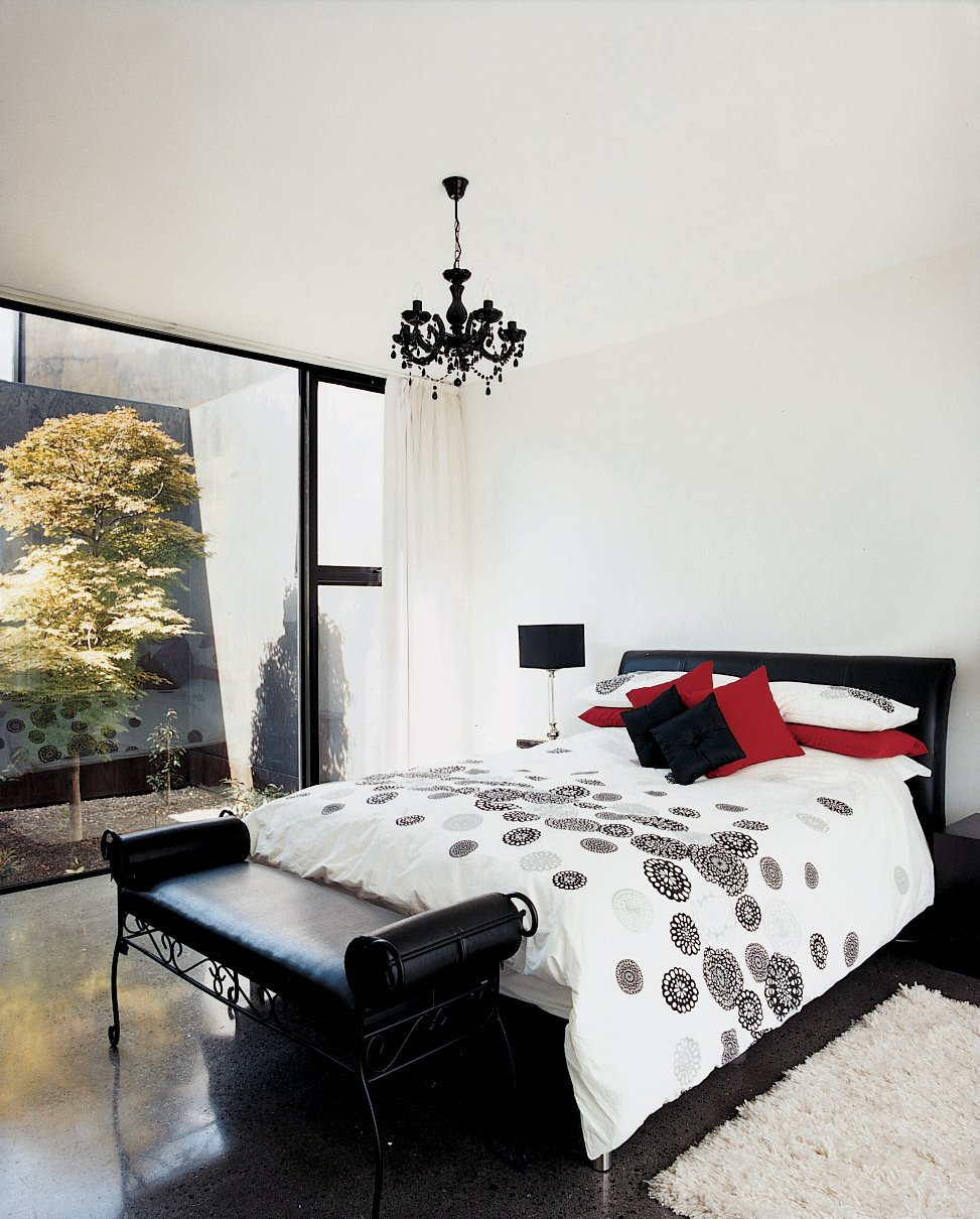 The decor of the master bedroom remains stark, but a black chandelier brings a touch   of complexity to an otherwise white space. The same maple tree can be seen through the rear glass wall, providing a visual focus for this wing of the house.  Photo 11 of 12 in Kingston Brio