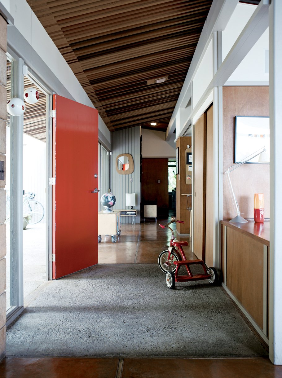 Hallway and Concrete Floor The Pfeiffers' furnishings tend to be of two stripes: flea-market treasures or prototypes and castoffs of Eric's design process. The low tables behind the front door are of Eric's design.  Photo 2 of 9 in Oakland Aesthetics