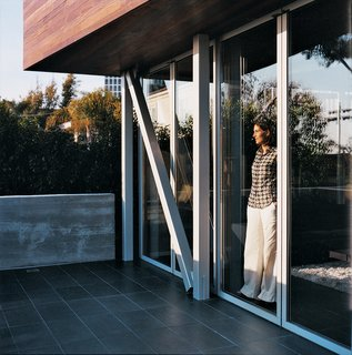 Maricarmen looks out toward the ocean from inside the sliding glass NanaWall.
