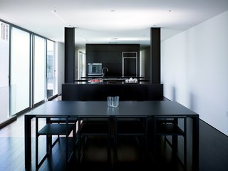 """The """"daytime"""" living quarters in the penthouse are dark, from the floor to the furnishings. The dining table is by Jasper Morrison for Cappellini (with an Aalto vase by Iittala on top). The chairs are by Ag Fronzoni also for Cappellini."""