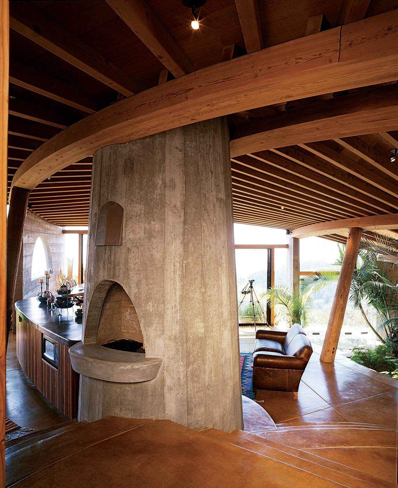 Living Room, Wood Burning Fireplace, and Sofa The interiors of many of Muennig's houses emphasize natural building materials such as wood, concrete, and stone. Plant life and nature are intrinsic to the Pfeiffer Ridge House IV.  Photo 1 of 9 in Big Sur: Coastal Commissions