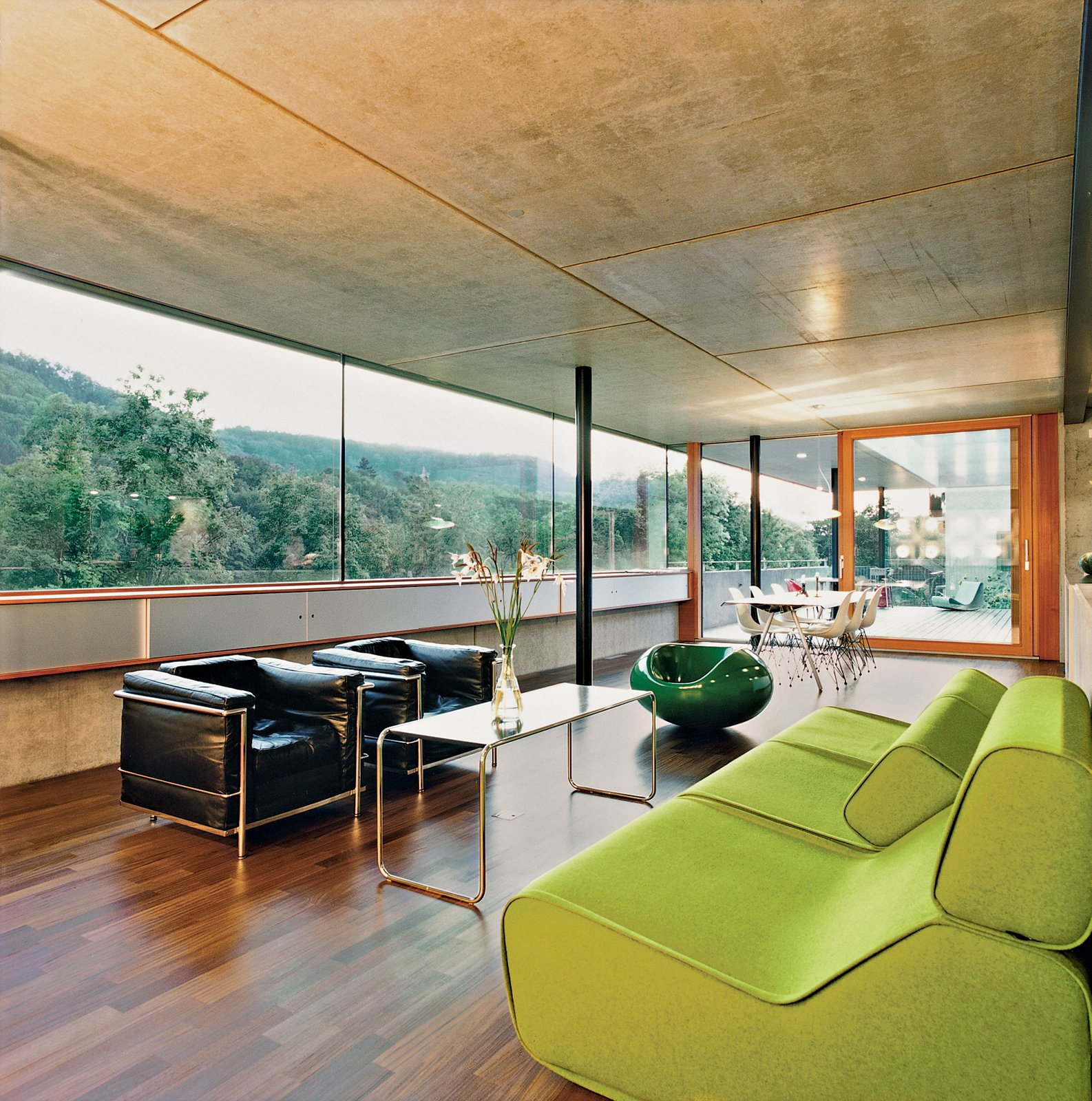 Living Room, Chair, Medium Hardwood Floor, Sofa, and Coffee Tables After walking through the front door visitors enter directly into the enormous kitchen and living space. The interior is minimal, using predominantly timber and concrete. It also provides some spectacular views of the river.  Futuristic Prefab Homes by Robert Gordon-Fogelson from Swiss Mix