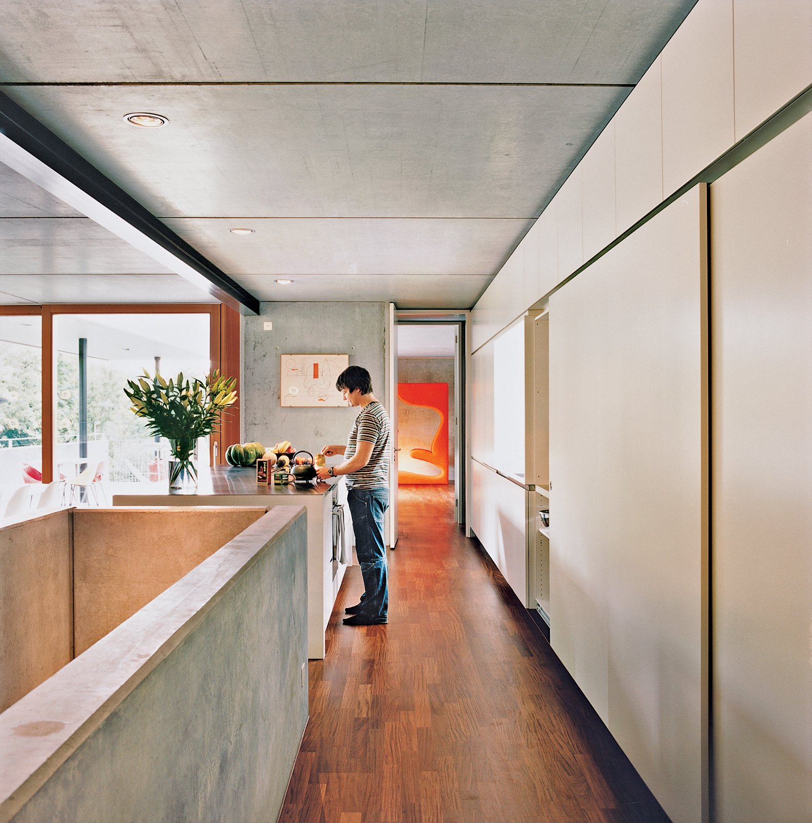 Kitchen, Concrete Counter, and Medium Hardwood Floor Meili makes tea in the kitchen. The Living Tower by Vernon Panton is in the background.  Photo 7 of 11 in Swiss Mix
