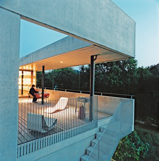 The couple do their outdoor lolling on Willy Guhl's concrete Loop chair (near grating) and Superieur's Divan lounge (near the table), both Swiss products.