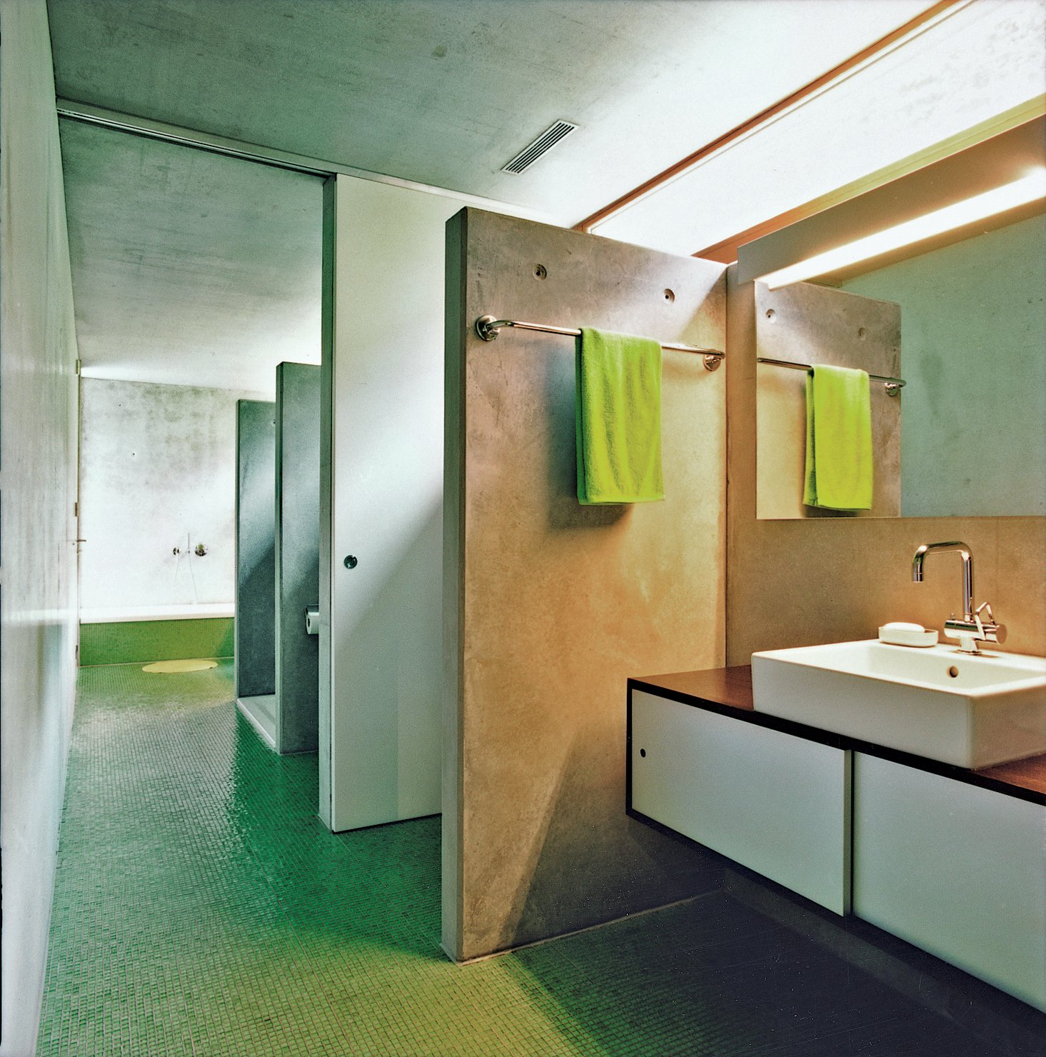 Bath Room, Vessel Sink, Ceramic Tile Floor, and Concrete Wall The bathroom is a long, linear space with a letterbox window to provide natural light. There are two toilets, a pair of sinks, and two showers.  Photo 9 of 11 in Swiss Mix