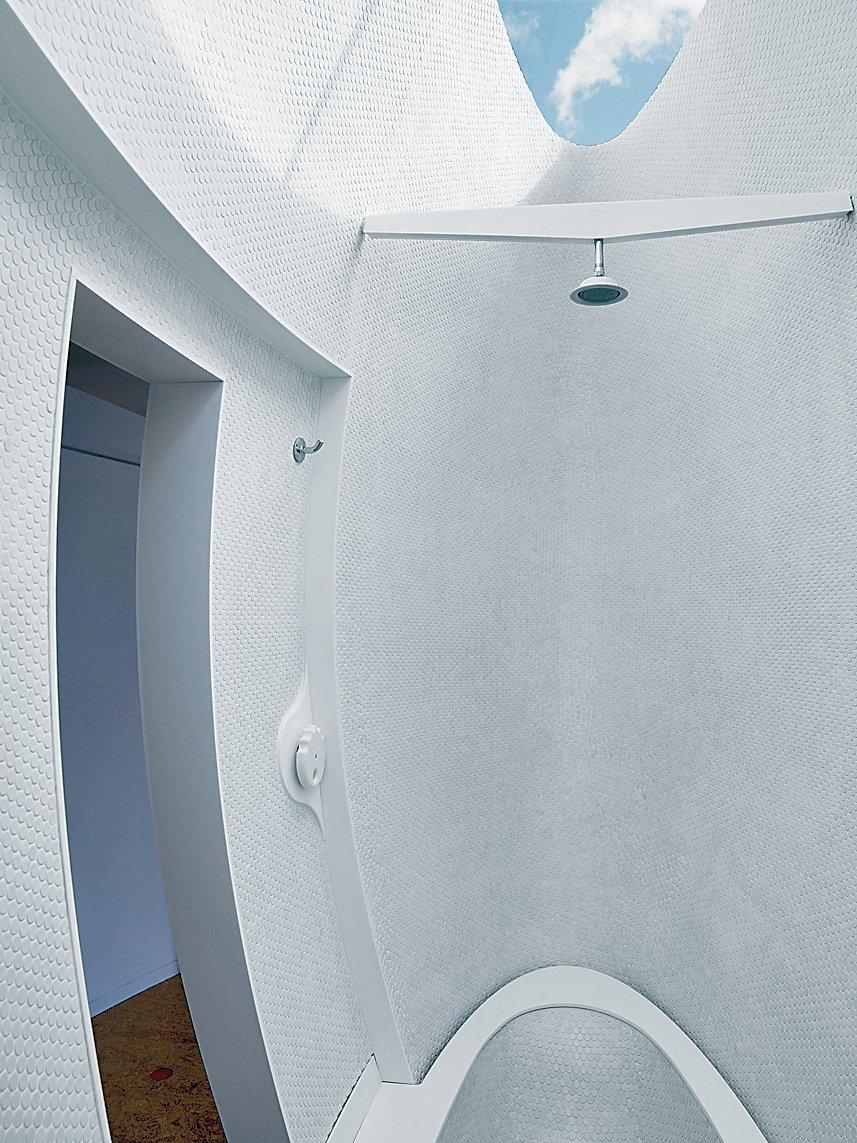 The curving exterior of the podlike bath and shower cuts an elegant form at the other end of the room.  Photo 10 of 11 in Massie Produced
