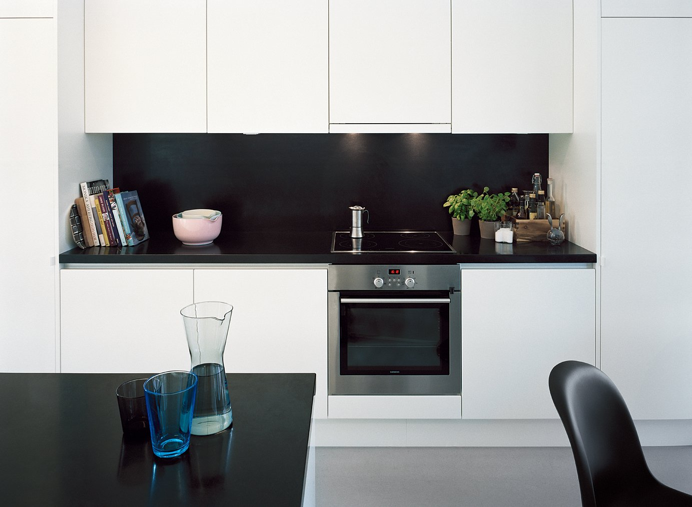 Kitchen, White Cabinet, and Laminate Counter Laminated-MDF cabinetry helps to hide clutter in the kitchen.  Photo 4 of 13 in Sum of Its Parts