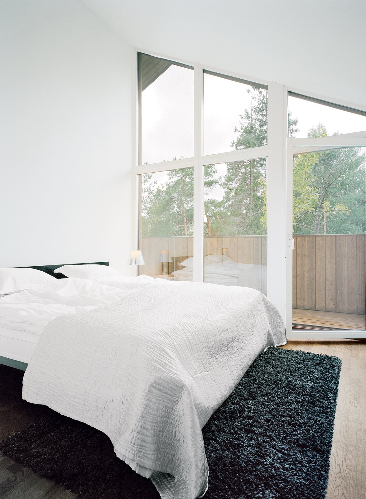 Bedroom and Bed Triangular windows beneath the roof line are a common element in all of the second-floor rooms, including the master bedroom.  Photo 12 of 13 in Sum of Its Parts