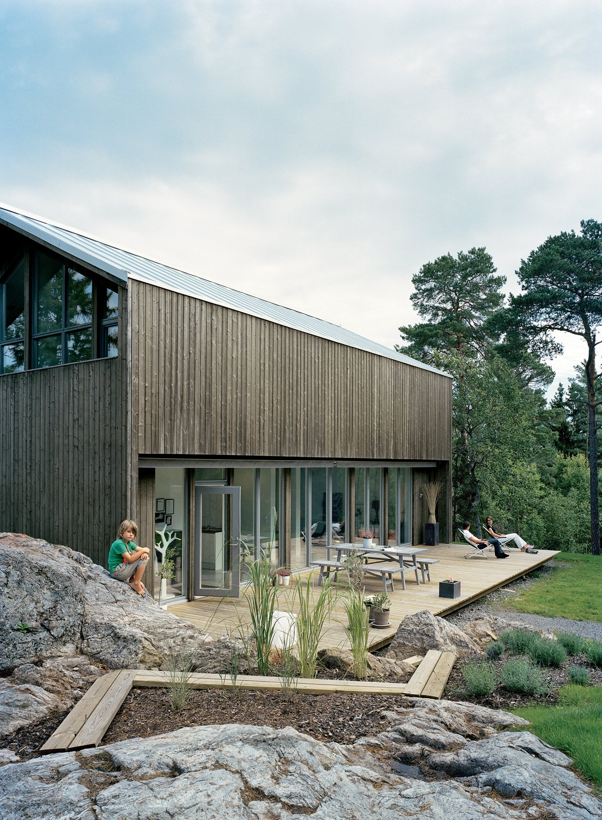 Outdoor, Wood Patio, Porch, Deck, Back Yard, Large Patio, Porch, Deck, and Grass On the wide deck, the family enjoys some peace and quiet.  Sourcing Guide for Modern Prefab Companies in Europe by Kelsey Keith from Sum of Its Parts