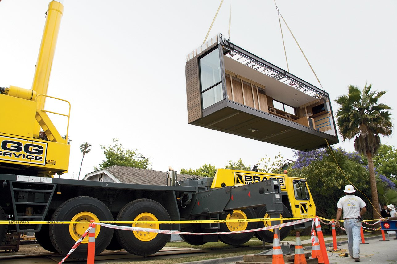 Once the completed modules arrive on-site, it's simply a matter of putting the pieces together. With the help of a large crane, workers hoist one module into place.  Marmol Radziner Prefab by Jessica Hundley