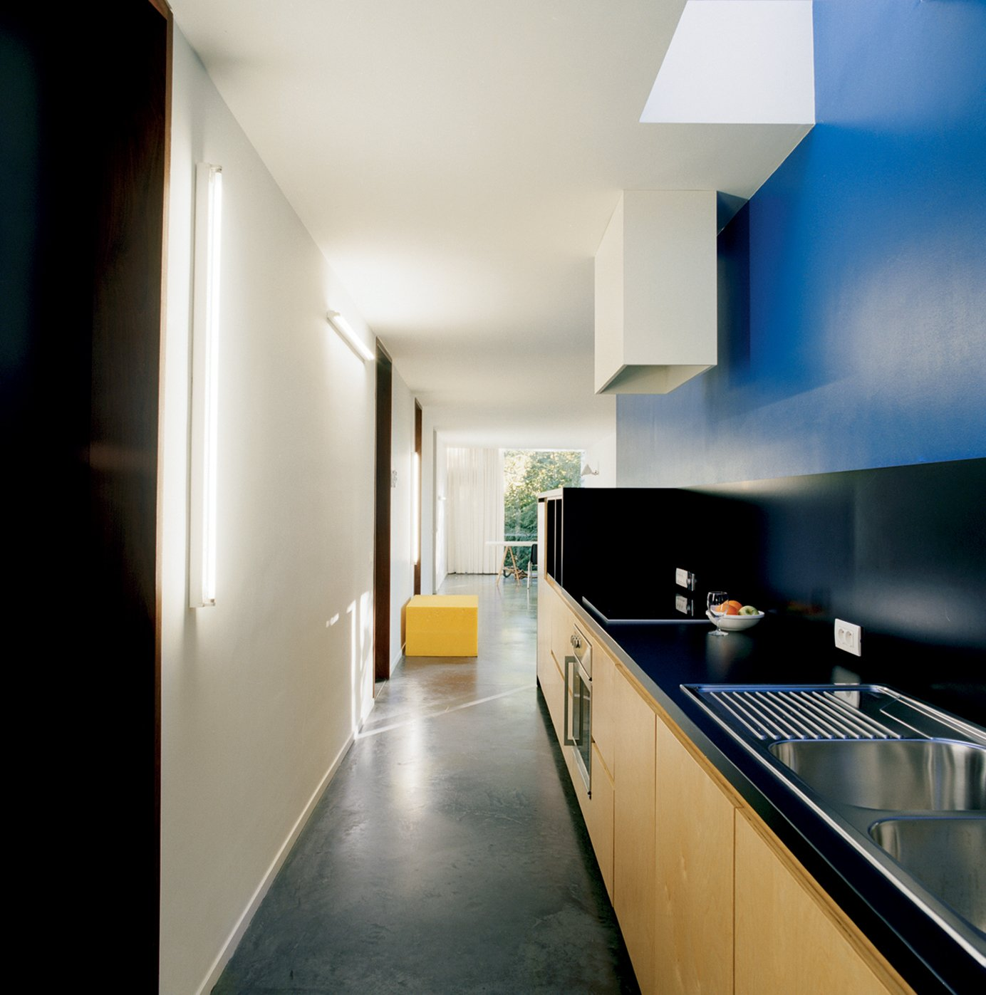 """Kitchen, Wood Cabinet, and Concrete Floor The kitchen is a vibrant deep blue. """"It's the same color Le Corbusier used in the corridor of his Villa Savoye in Poissy,"""" Van Everbroeck reports.  Photos from The Tree of Ghent"""