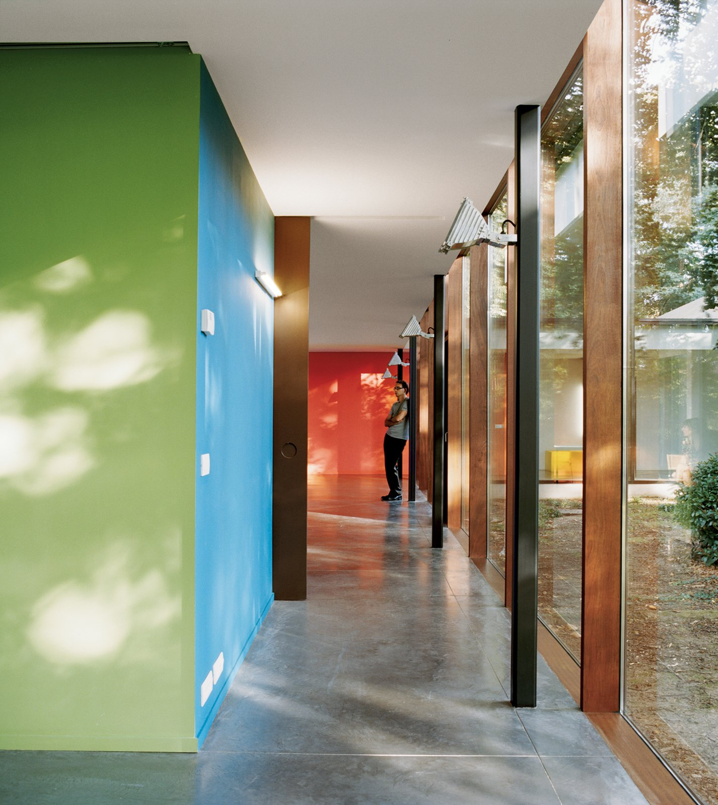 Hallway and Concrete Floor Inside the home green and blue are used for the bathroom block, dark brown for the sliding door, and orange for the wall dividing the living room from the kitchen. The floor is dark gray industrial poured concrete.  Composition