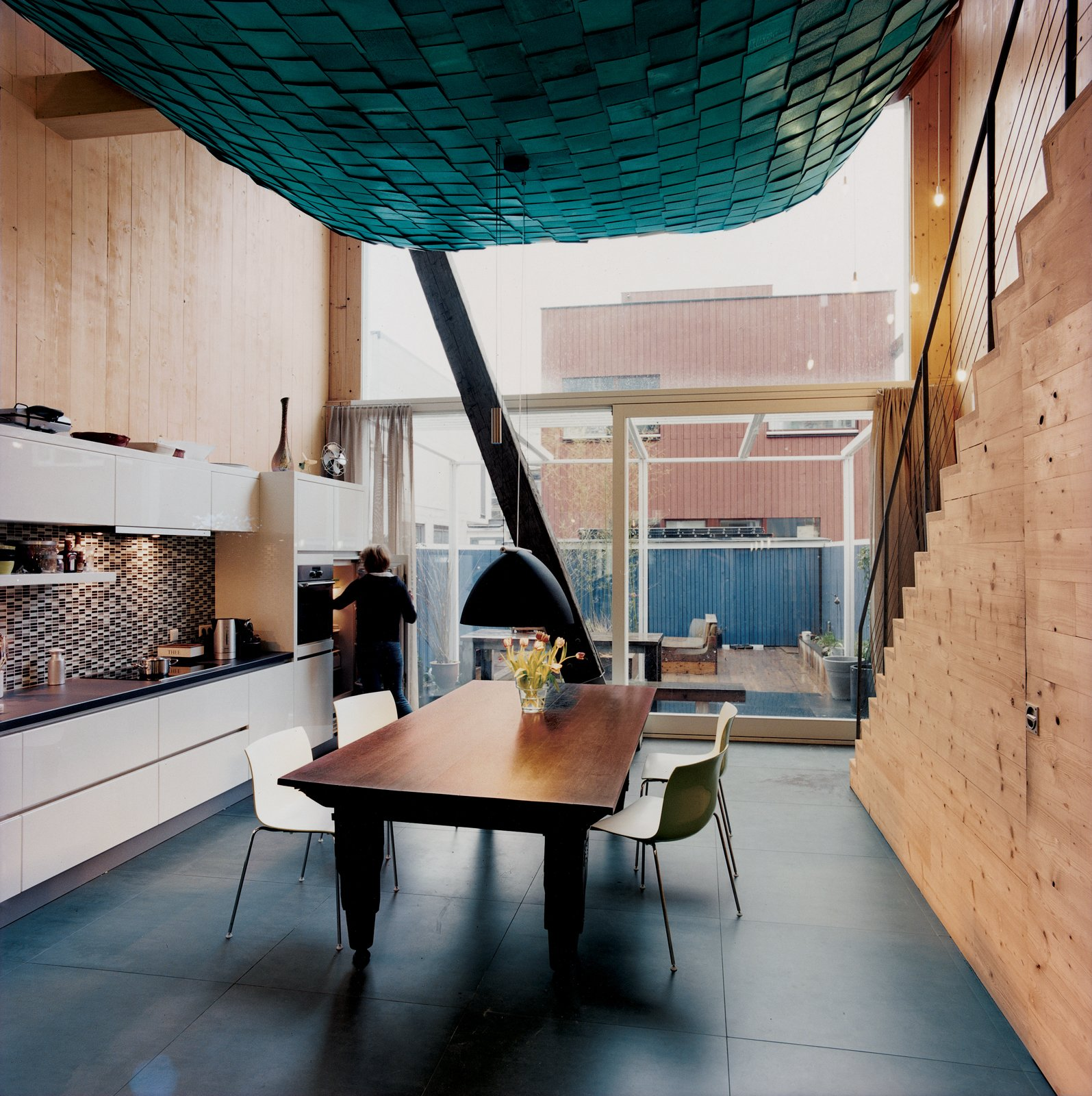 The suspended living room's scaly belly doesn't detract from the unfussy kitchen and dining area. A recycled Berlage-era table base (with a new tabletop), a deep blue lamp, and Arper chairs add to the maritime feel of the house.  Photo 5 of 10 in A Suspended Living Room Floats Like an Air Ship