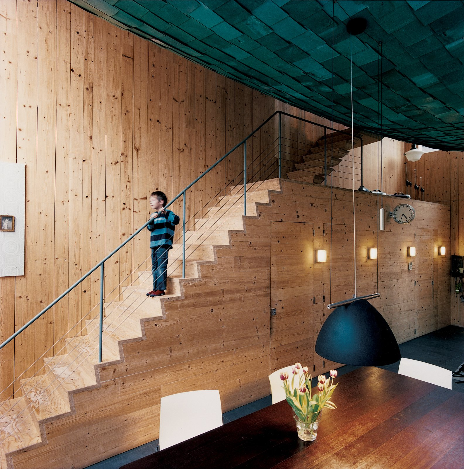 Staircase, Metal Railing, and Wood Tread Ceramic floors with radiant heating and cozy wall sconces top off the distinctive appearance, smell, and sound.  Photo 1 of 10 in A Suspended Living Room Floats Like an Air Ship