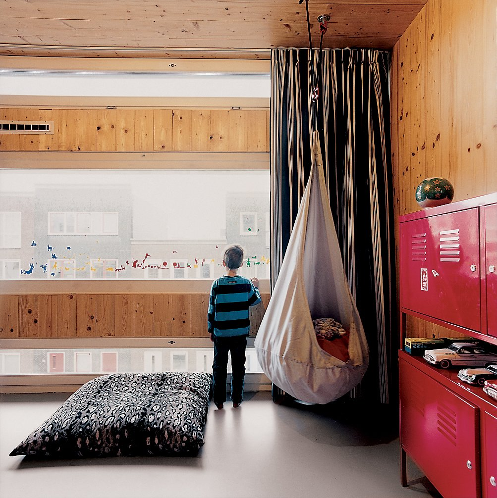 Kids Room, Bedroom Room Type, Pre-Teen Age, Boy Gender, Shelves, and Storage Finn's street-facing room at the front of the house is enlivened by varying window sizes.  Photos from A Suspended Living Room Floats Like an Air Ship