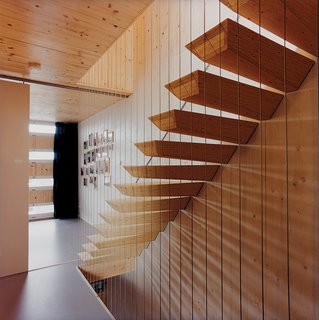 """These stairs mimic the magic of """"the ship""""—a floating living room in the home— by appearing to float without support. """"I drew the stairs like this, but I had no idea how to construct them,"""" says architect and homeowner Pieter Weijnen, laughing. Project builder Jasper Kerkhofs came to the rescue, using two iron rods to fix each stair to the wall. Steel cables were added to guard the sides of the staircase."""