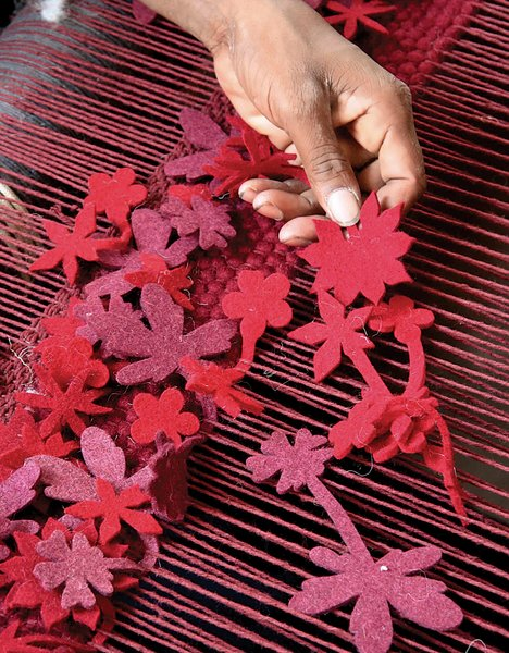 SPN Carpets, which is on the outskirts of Delhi, is the company that Nanimarquina tasks to manufacture their Boontje-designed rug, Little Field of Flowers. Here, a technician holds up a flower before it's tucked into the loom.