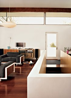 Clerestory windows, in combination with a glazed door, allow natural light to penetrate into this living room.