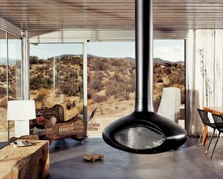 The iT House brings together raw industrial aesthetics with the tactics of green design to forge a new home in the sunbaked wilds of California's east. In a living space with floor-to-ceiling windows, a suspended fireplace by Fire Orb provides a shared hearth for friends and family to gather around.
