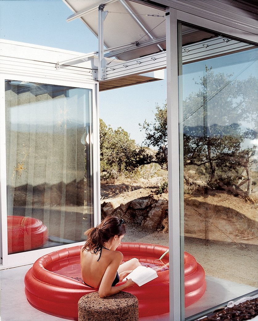 "Outdoor, Small Pools, Tubs, Shower, and Desert The living space and bedrooms are separated by two small courtyards. Linda Taalman reclines in a small, inflatable wading pool in the home's ""firecourt,"" facing south toward the desert.  Outdoor Living from iT House, Joshua Tree"