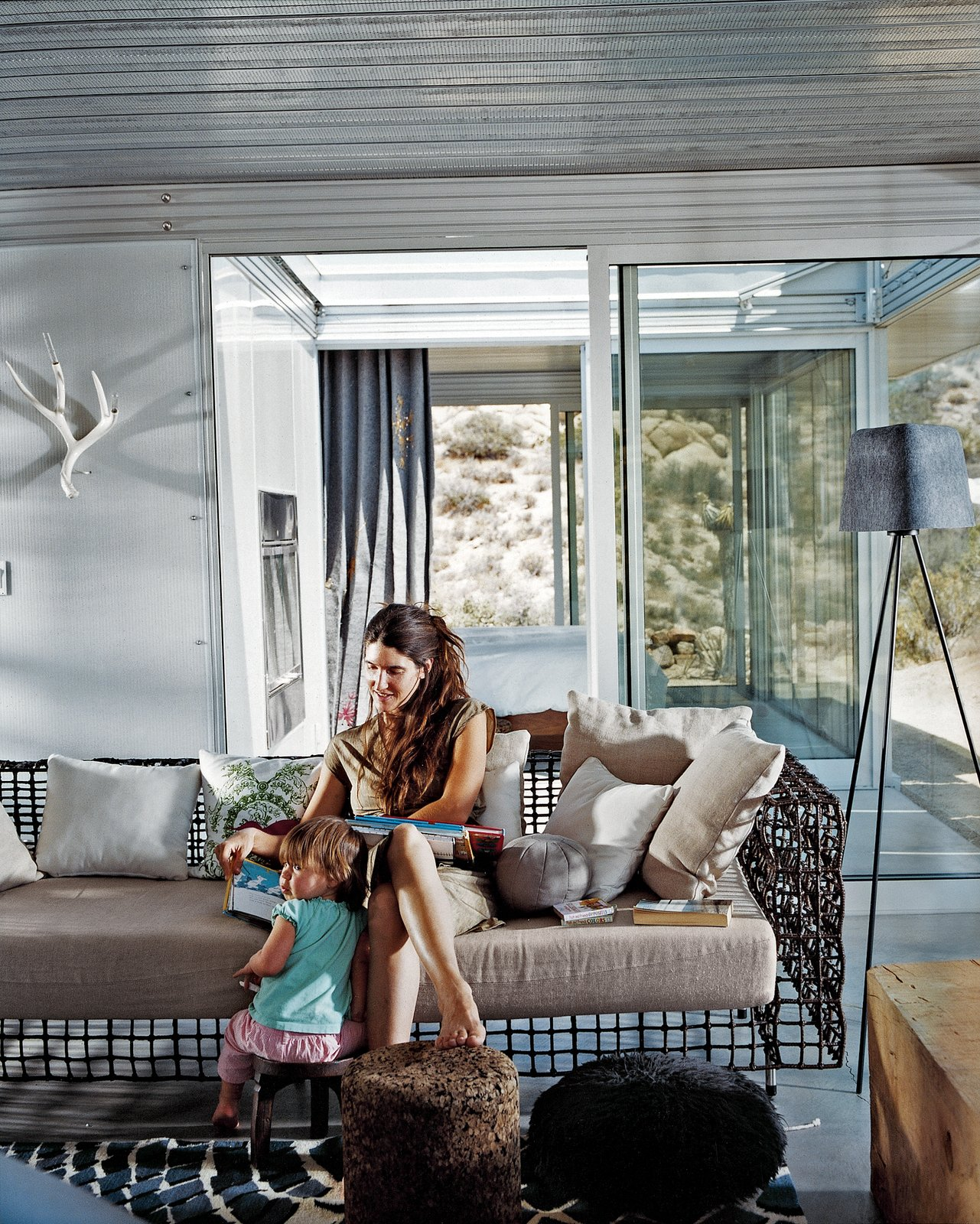Living Room, Sofa, Floor Lighting, and Concrete Floor Taalman sits with their daughter, Oleana, in the living room on a metal lounge designed by Kenneth Cobonpue. Glass walls emphasize views and greatly expand the sense of space in the 1,100-square-foot house. Through the glass wall behind her is the fire court and behind that the master bedroom.  Photo 7 of 9 in iT House, Joshua Tree