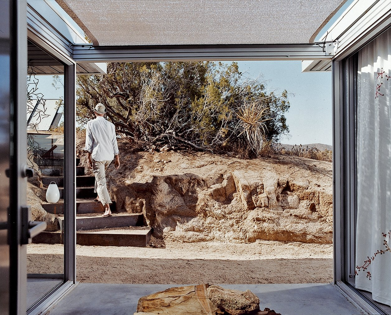 Outdoor, Small Patio, Porch, Deck, and Concrete Patio, Porch, Deck A view out from the entrance lobby shows Koch leaving the house. He made the stairs' steel risers himself, with the help of his cousin, Chris Wilson.  Photo 9 of 9 in iT House, Joshua Tree