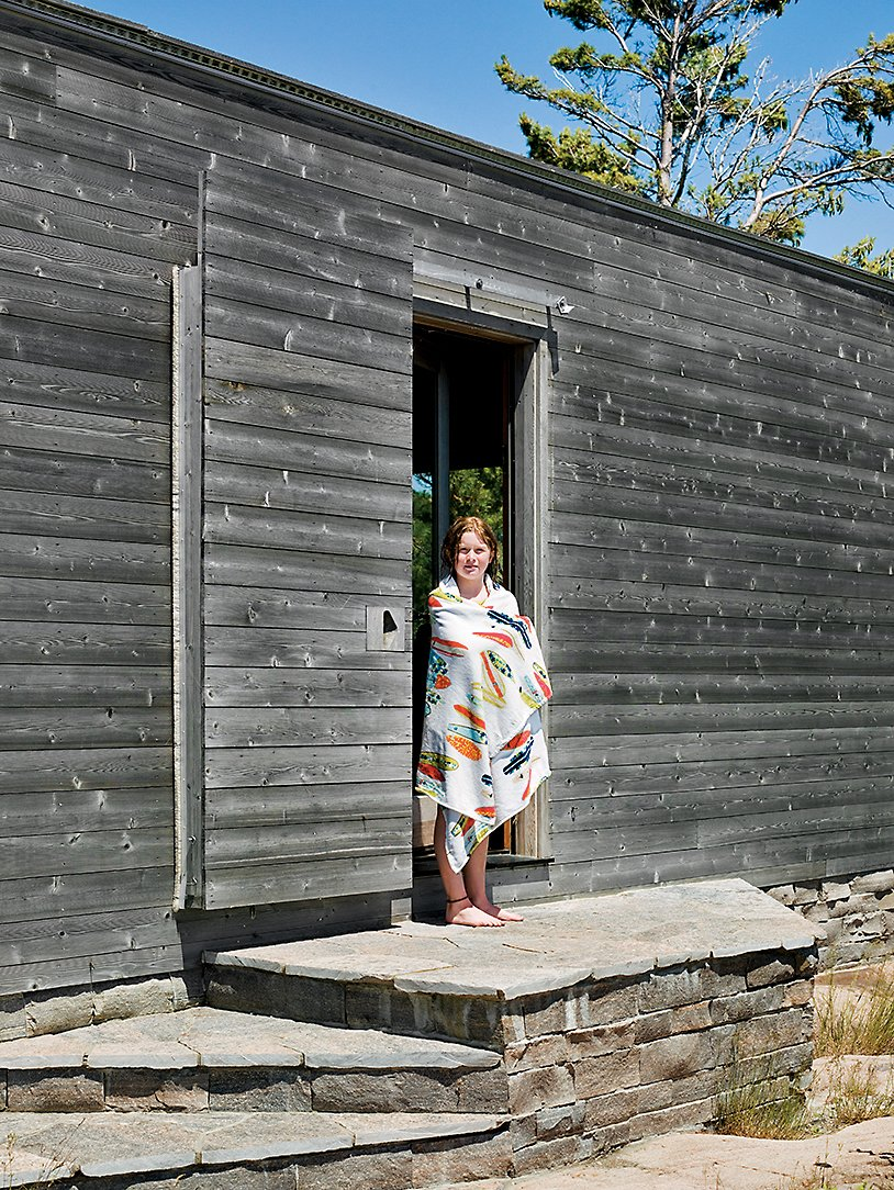 Emma Worple dries off from a swim at the cedar-clad sleeping cabin; the door slides shut to shield the cabin from harsh winter winds.  Photo 2 of 16 in Floating House, Lake Huron
