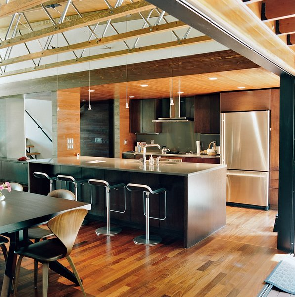 The couple opted for a smaller kitchen without fussy appliances and a larger dining area. They concentrated on achieving a high-quality space through carefully chosen furnishings, including the Cross Extension table in wenge, a Cherner side chair, and the LEM Piston stools, all from Design Within Reach.
