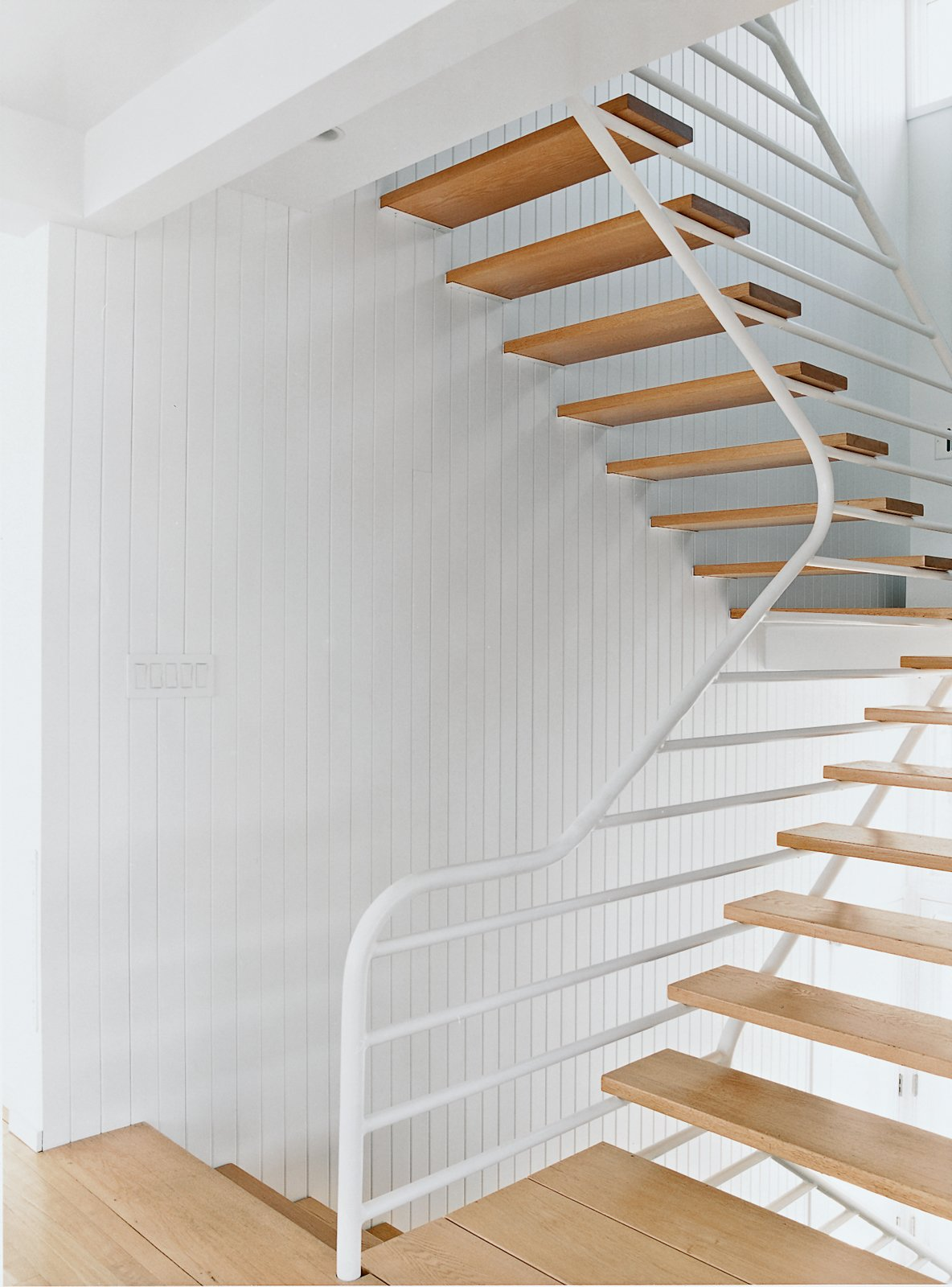 The main staircase consists of simple oak treads that cantilever out from side walls sheathed in natural vertical board and are supported on the other side by a continuous grill-like railing truss.  Photo 3 of 8 in Bauhaus by the Sea