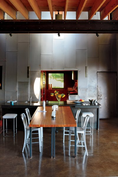 "A custom recycled-Douglas fir table by VanEyk Custom Woodworks is the heart of the living-dining room in the so-called ""Scrap House."" The double-height wall is clad in the same steel that wraps the exterior. Read the full article here."