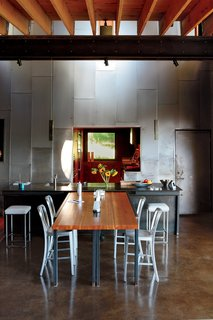 """A custom recycled-Douglas fir table by VanEyk Custom Woodworks is the heart of the living-dining room in the so-called """"Scrap House."""" The double-height wall is clad in the same steel that wraps the exterior. Read the full article here."""