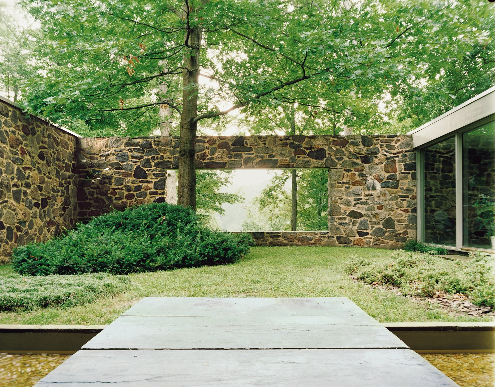 A large rectangular cut in the back wall of the house creates views from the entrance through a courtyard to the trees and lake beyond.  Photo 2 of 9 in Marcel Breuer Hooper House II