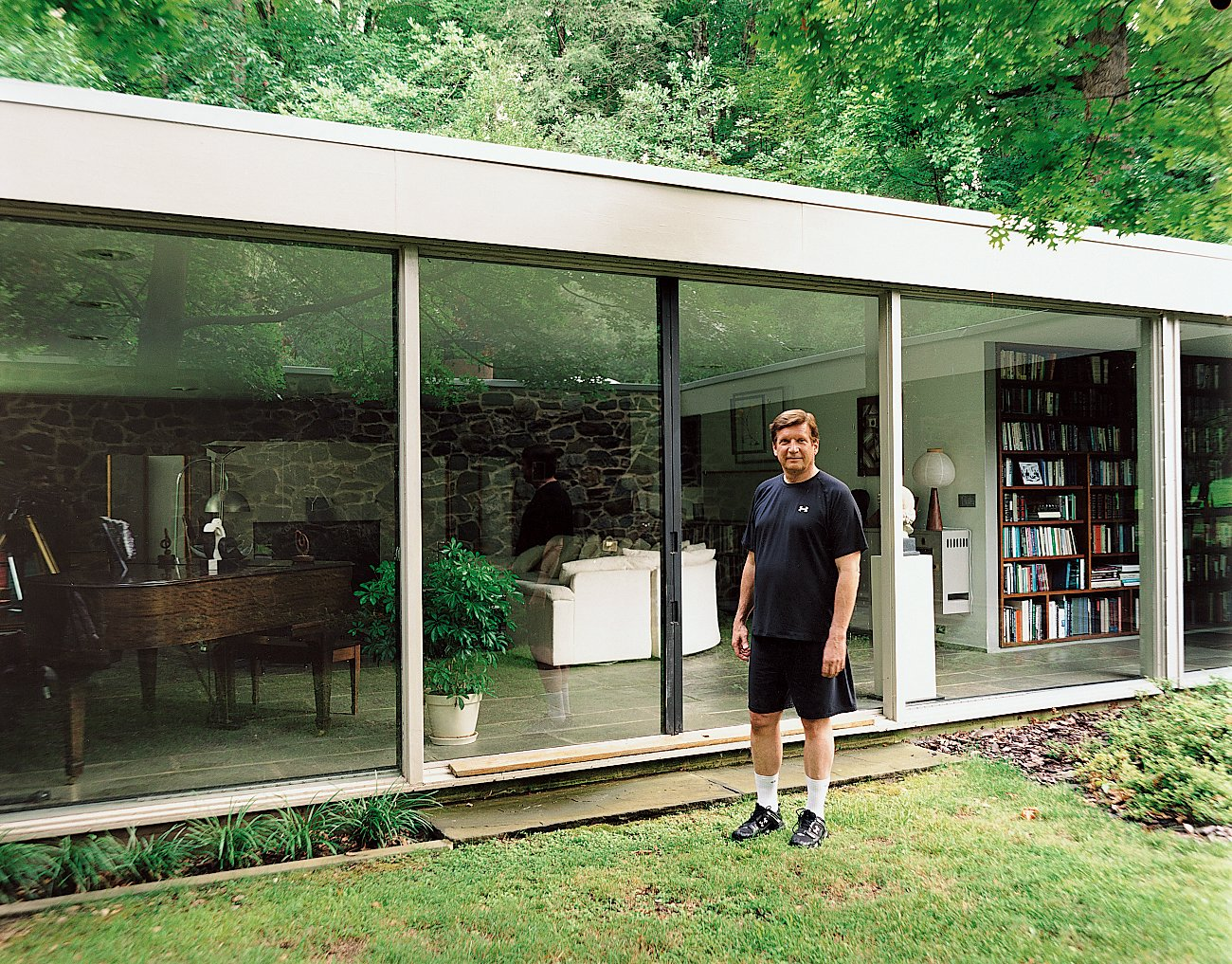 North stands outside his glass-walled living room, which also houses his small library of books about Breuer.  Photo 3 of 9 in Marcel Breuer Hooper House II