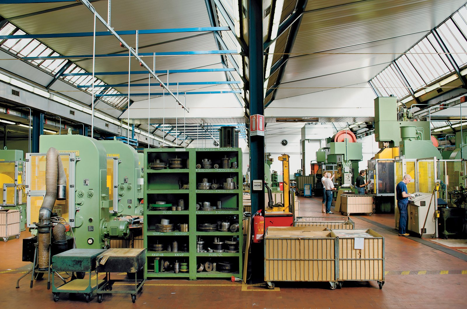 The factory contains a wide array of hydraulic presses. The cagelike bins hold groups of cold-pressed objects left ready for the next phase of production. Alessi's facility manufacture fifty-thousand 9090's per year.  The Alessi 9090 by Virginia Gardiner