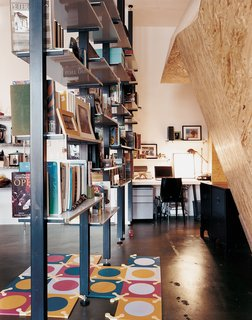 Custom-fabricated modular bookshelves create a corridor leading to the home office.