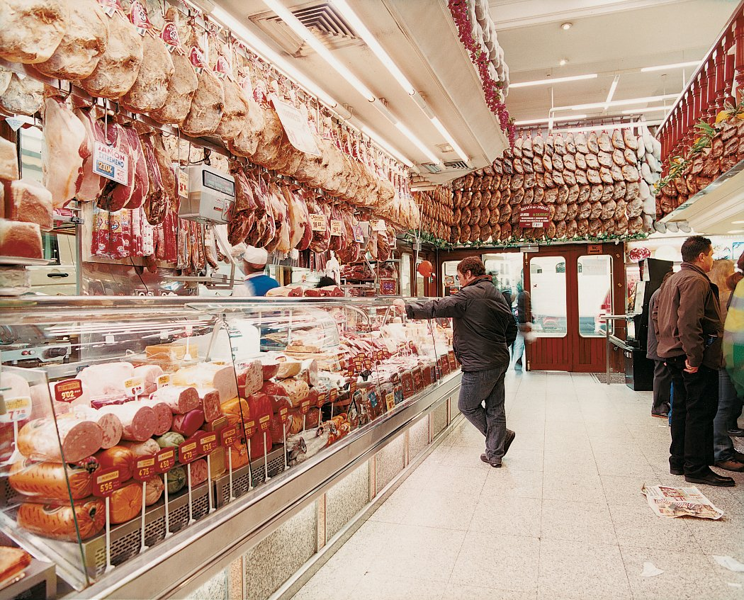 """Cured ham hocks dangle from the ceiling of Museo del Jamón, celebrating Spain's famed Serrano ham culture.  Search """"culture"""" from Architecture Tour: Madrid, Spain"""
