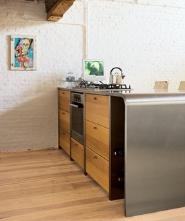 Teak cabinets add warmth to the steel counter in the kitchen, which local designers Op16 created for the couple. The picture was bought in Mexico. Exposed electricity cables on the old brick walls enhance the industrial feeling.