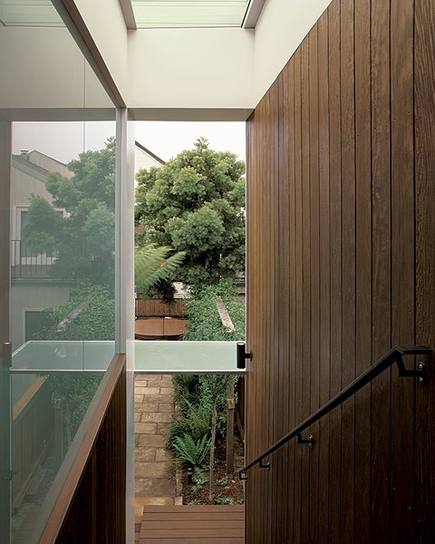 The sheltered stairway, bordered on one side by glass and on the other by ipe planks, creates a gentle descent from the garage to the garden.