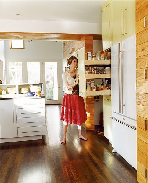 The kitchen links the new and old parts of the house; fittingly, its style is somewhere between traditional and modern. A kitchen wall makes room for a fridge and roll-out shelving.