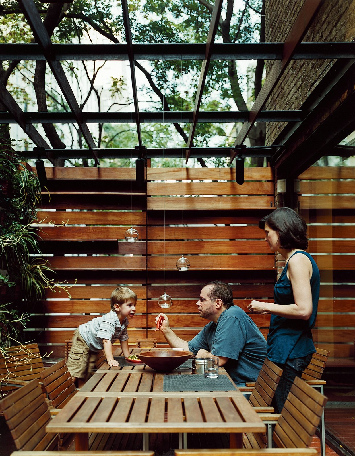 An outdoor dining area is screened for privacy.  Outdoor