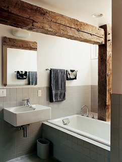 Rather than concealing the barn frame in the private rooms, Cohen created an interplay between modern and historic elements in the master bathroom.